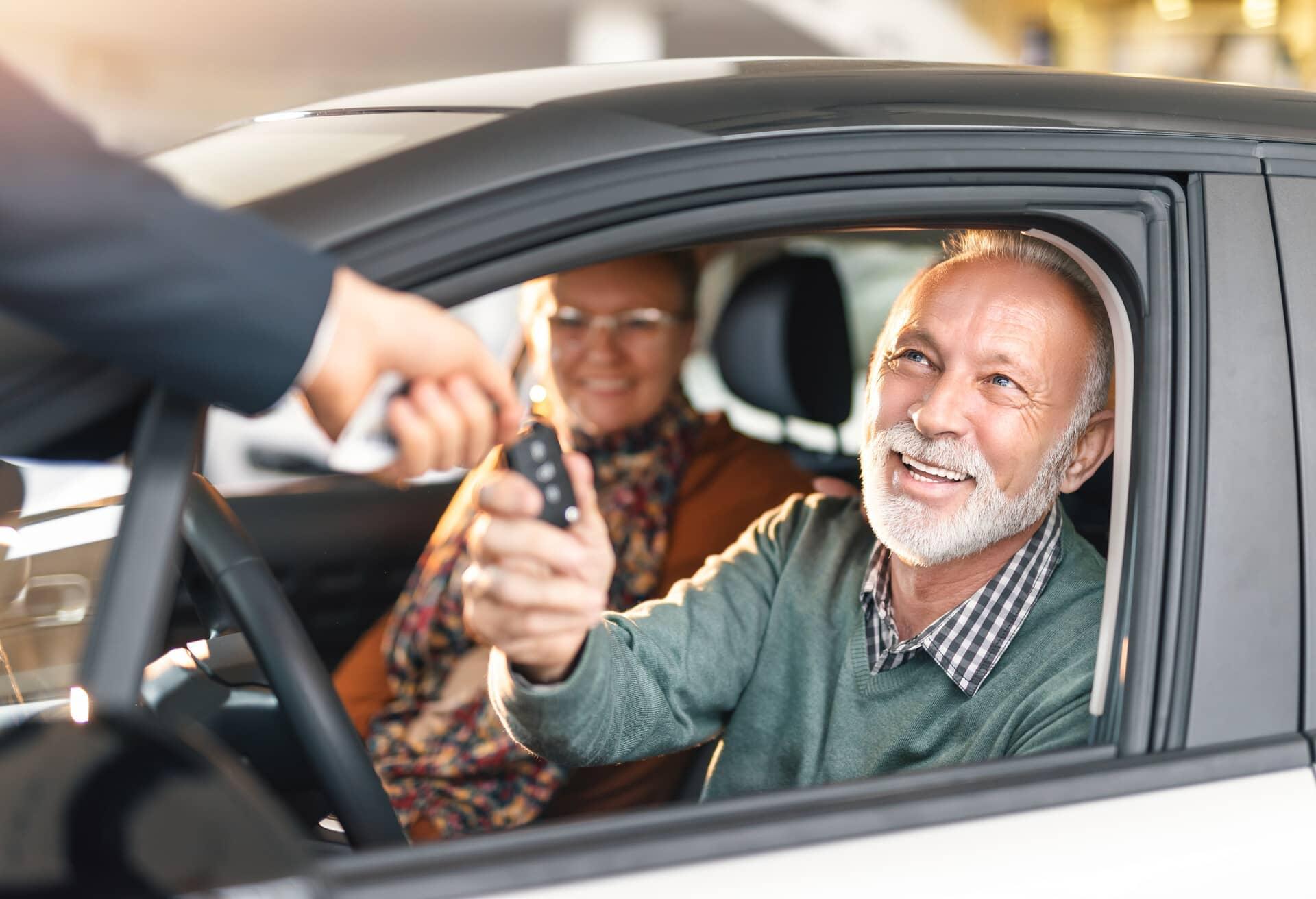 Ein älteres Paar, das im Auto fährt.