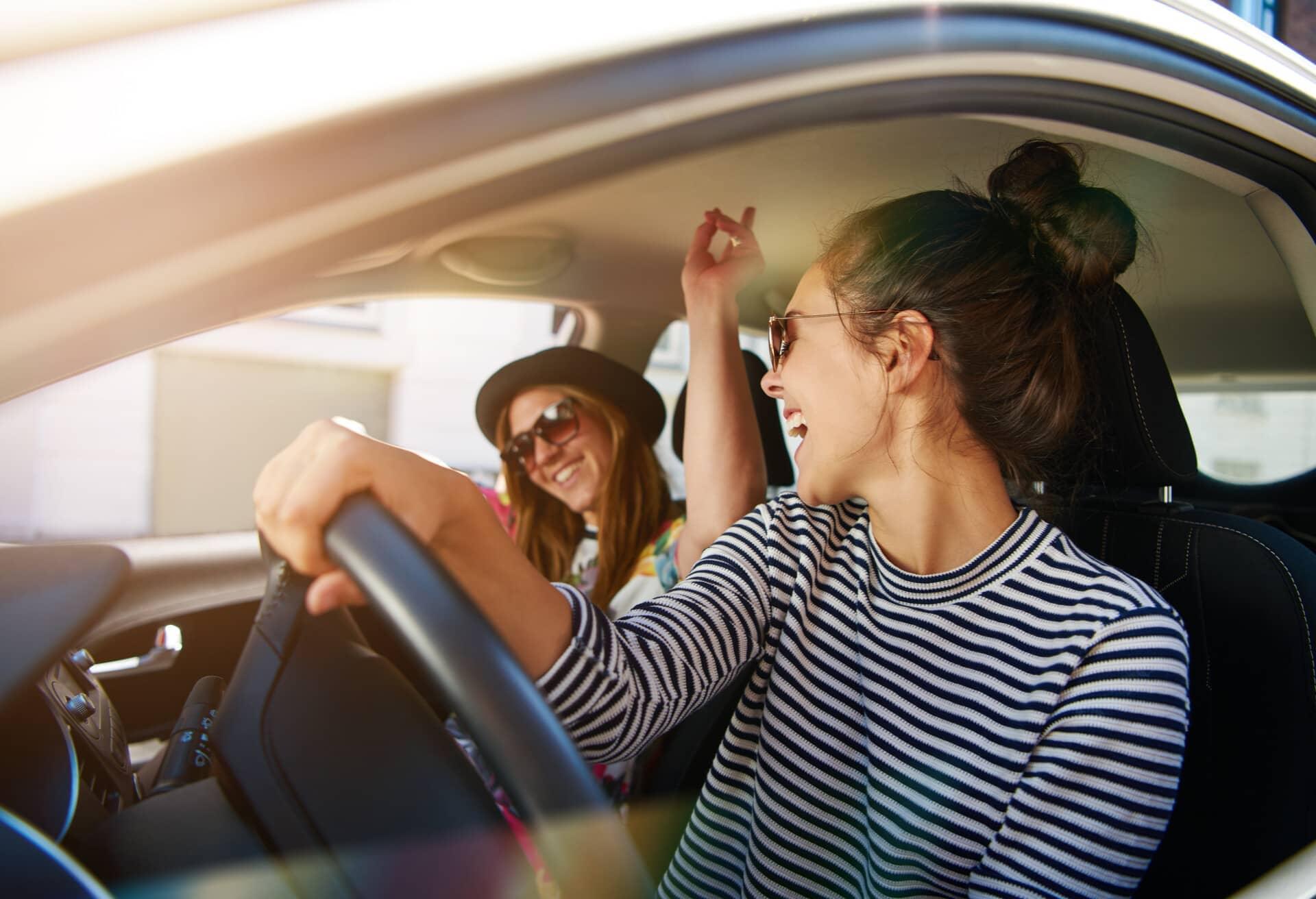 Freundinnen und Freunde, die während eines Roadtrips Spaß haben.