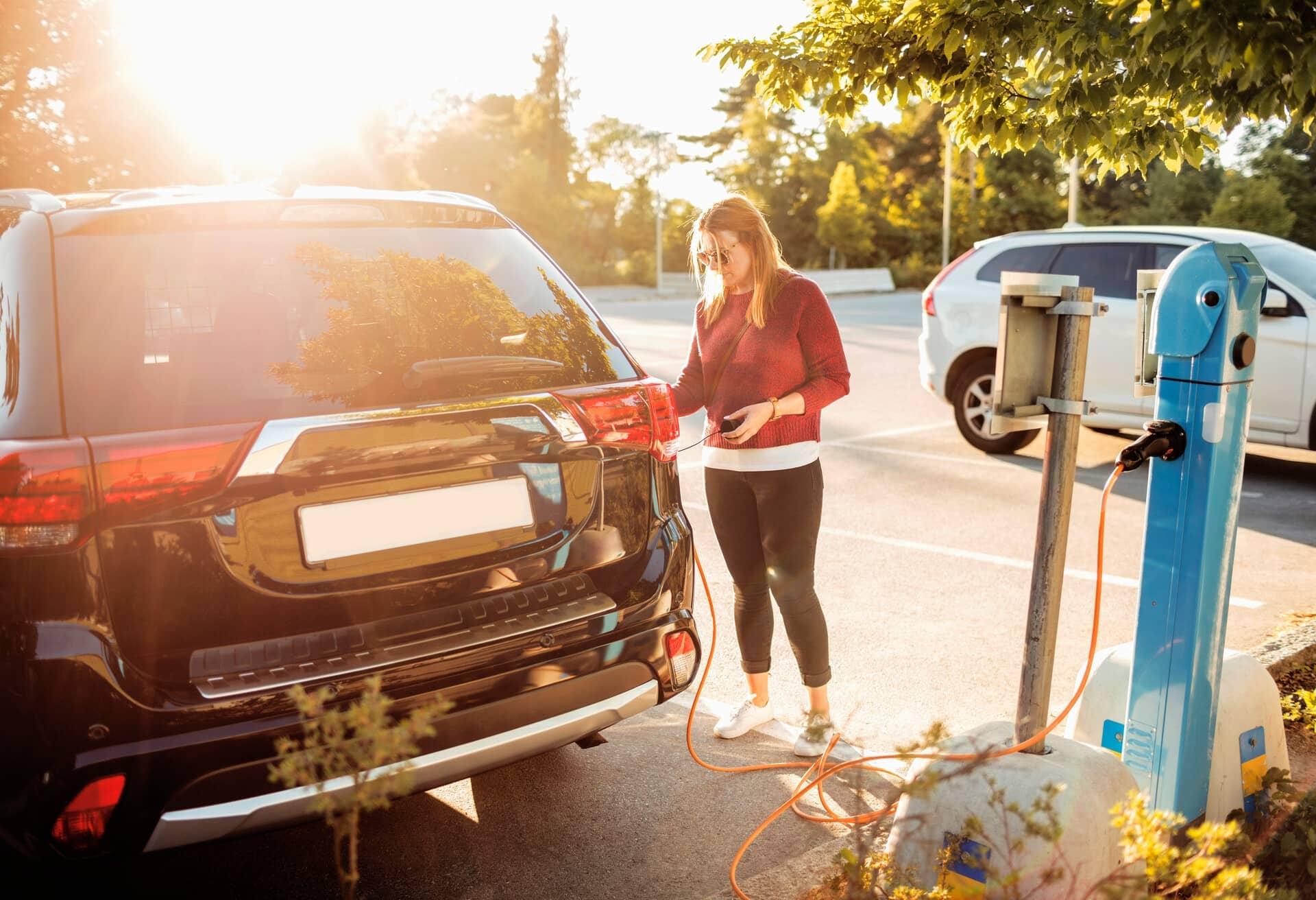 Eine junge Frau, die ein Elektroauto aufladen möchte.